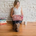 Woman with an opened laptop writing for her website.